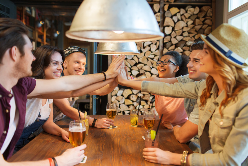 happy friends with drinks making high five at bar